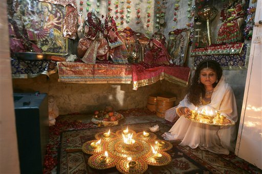 Pakistani Hindu lighting diyas for Diwali